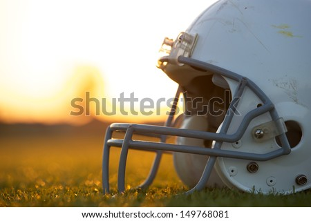American Football Helmet on the Field at Sunset with room for copy - stock photo