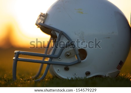 American Football Helmet on the Field backlit by the Sunset - stock photo