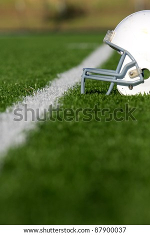 American Football Helmet on the Field with room for copy, shot with shallow depth of field - stock photo