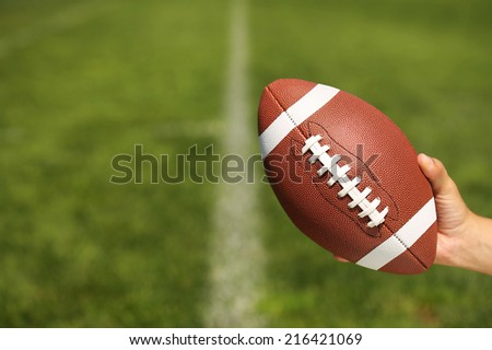 American Football in Hand over Field with yard lines - stock photo