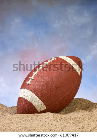 American football in the sand on the beach with blue background - stock photo