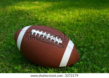 American football isolated on top of green grass - stock photo