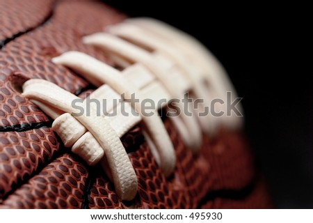 american football - macro over black with shallow depth of field and focus on first seam - stock photo