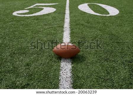 American football near the fifty yard line - stock photo