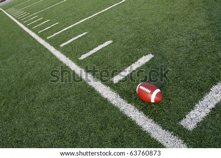 American Football near the yard lines of a field angled for effect - stock photo