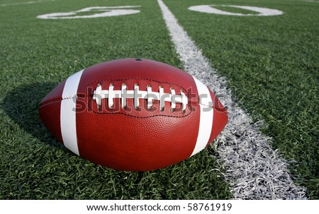 American Football on filed with the Fifty Yard Line Beyond - stock photo