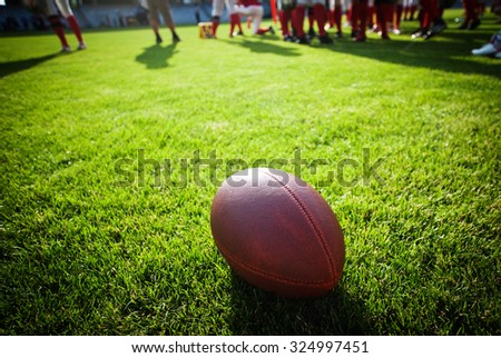 american football on stadium with out of focus players in the background - sport concept