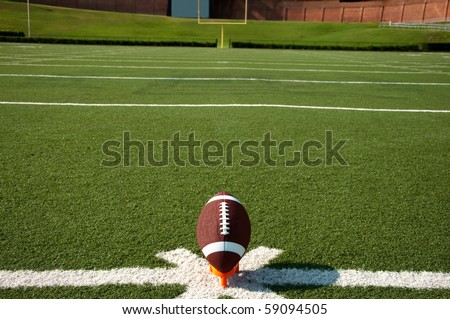 American football on tee on field with goal post in background. - stock photo