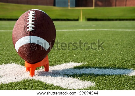 American football on tee on field with goal post in background.