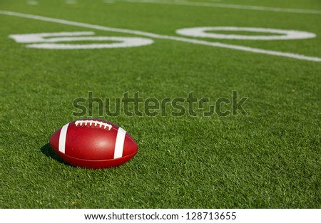 American Football on the Field near the Fifty Yard Line - stock photo