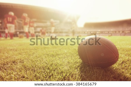 American football on the field, players in the background - stock photo