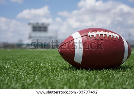 American Football on the Field with the stands in the background - stock photo