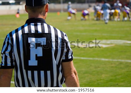 American Football played by young men with game official field judge referee - stock photo