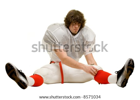 American football player. Adjusting uniform while stretching. - stock photo