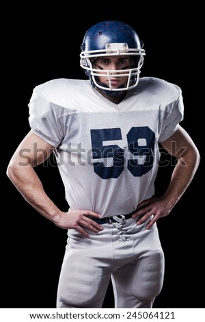 American football player. American football player looking at camera and holding hands on hips while standing against black background  - stock photo