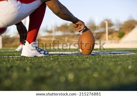 American football player attempting to kick field goal, teammate holding ball vertically against pitch (surface level) - stock photo