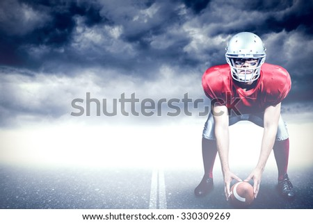 American football player bending while holding ball against stormy sky over road - stock photo