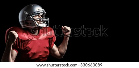 American football player cheering with clenched fist against black