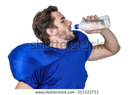 American football player drinking water against white background