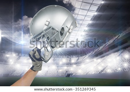 American football player handing his helmet against sports arena