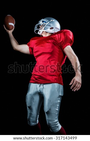 American football player holding ball against black background - stock photo