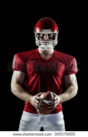 American football player holding ball on black background