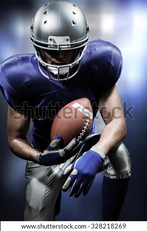 American football player holding ball while kneeling against white lights glowing - stock photo
