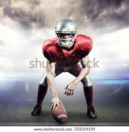 American football player holding helmet against american football arena - stock photo