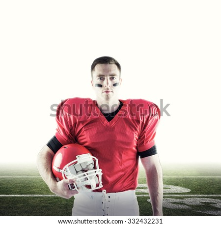 American football player holding helmet against american football pitch - stock photo