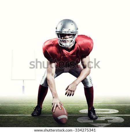 American football player holding helmet against american football posts - stock photo
