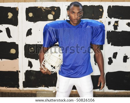 American football player holding helmet, portrait - stock photo