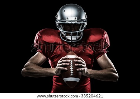 American football player in red jersey and helmet holding ball against black - stock photo