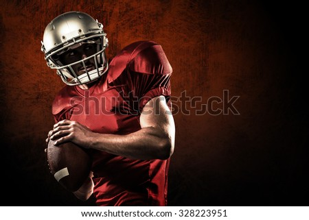 American football player in red jersey looking away while holding ball against dark background