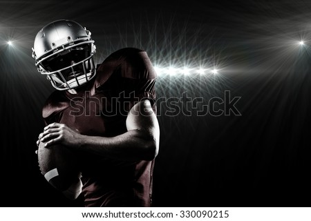 American football player in red jersey looking away while holding ball against spotlight