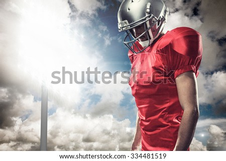 American football player in red jersey looking down against spotlight in sky