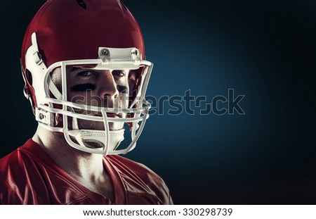 American football player looking at camera against blue background with vignette