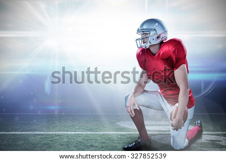American football player looking away while kneeling against american football arena
