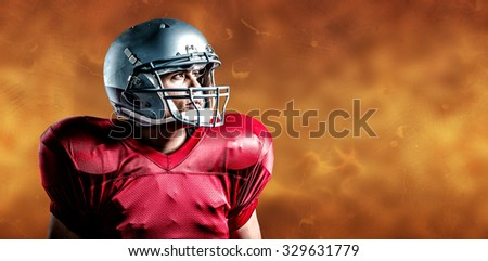 American football player looking away while standing against orange background