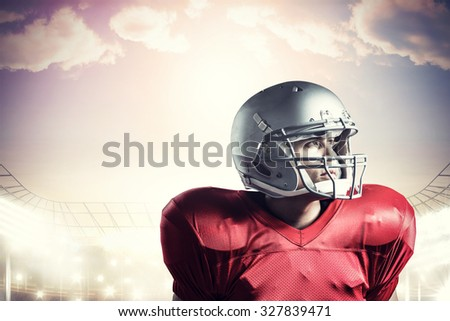American football player looking away while standing against rugby stadium