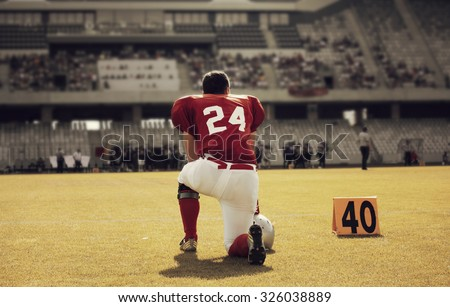 American football player on its knee - retro styled photo - stock photo