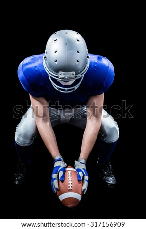 American football player placing ball while looking down against black background - stock photo