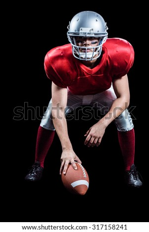 American football player placing ball while playing against black background - stock photo