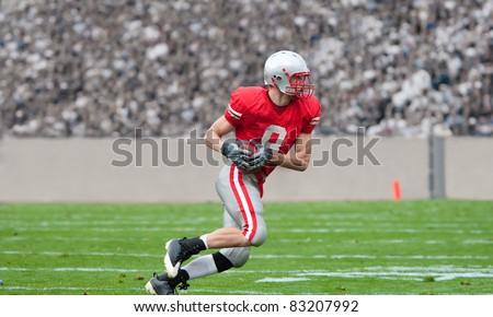 American Football Player running upfield - stock photo