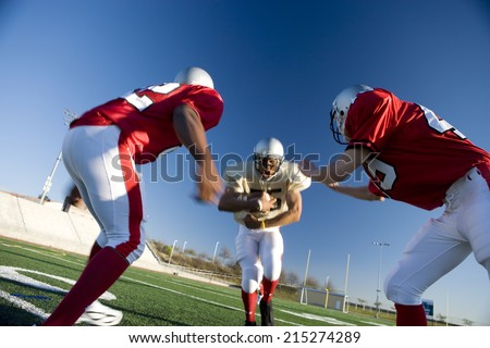 American football player running with ball at opposing team during competitive game (surface level, tilt) - stock photo