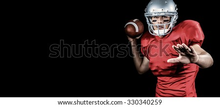 American football player throwing ball against black - stock photo