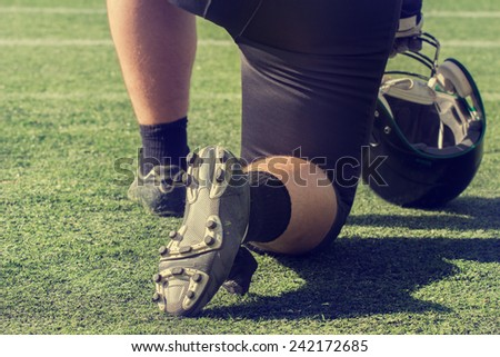 American football player waiting to join the game. - stock photo