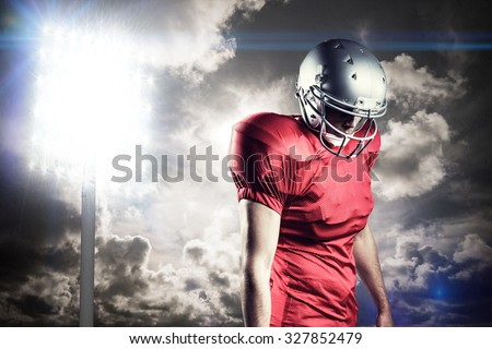 American football player with ball looking down against spotlight in sky