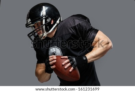 American football player with ball wearing helmet and jersey  - stock photo