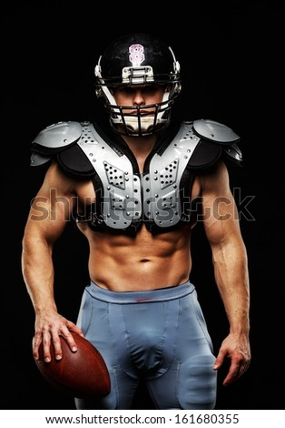 American football player with ball wearing helmet and protective shields  - stock photo