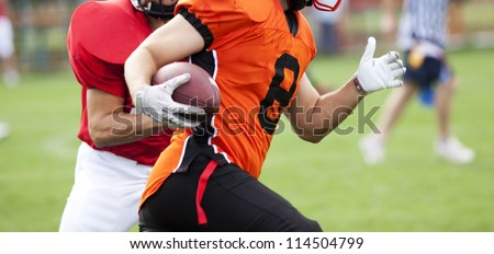 American football players fighting for the ball - stock photo
